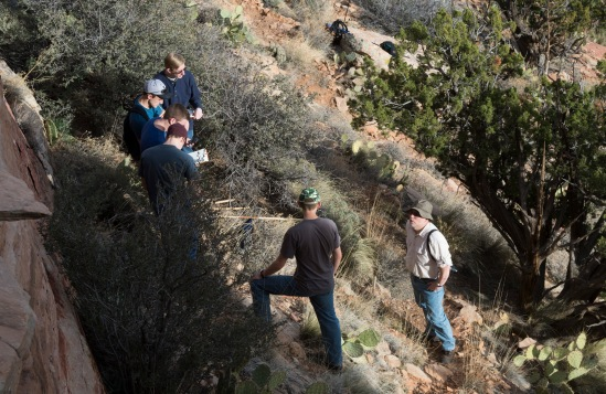 Dr. John Whitmore talks with students about what they are seeing in the rock formations.