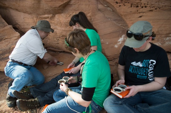 Dr. Whitmore instructing some students on how to use a brunton compass.