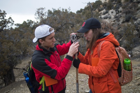 Ryan shows Victoria how to sight down a Brunton Compass with a Jacob Staff to measure rock layer thickness.
