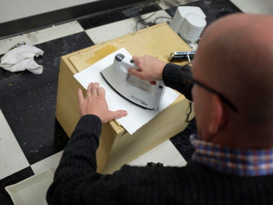 Use a hot iron and gently heat the paper moving the iron continual motion.
